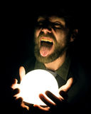 Bearded man in the dark, holding in front of a lamp, expresses different emotions Stock Photos