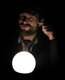 Bearded man in the dark, holding in front of a lamp, expresses different emotions. shows the index finger Stock Photography