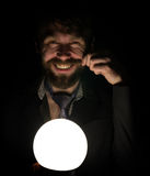 Bearded man in the dark, holding in front of a lamp, expresses different emotions. twirling his mustache with your Royalty Free Stock Images