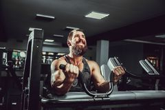 Man Doing Heavy Weight Exercise For Biceps On Machine In A Gym. Bearded Man Doing Heavy Weight Exercise For Biceps On Machine In A Gym Stock Photos