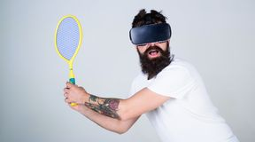 Bearded man doing sports in virtual reality. Hipster in VR headset with tennis bat  on gray background. Man with. Bushy beard playing computer simulated tennis Royalty Free Stock Photo
