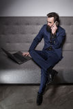 Bearded man dressed in suit and with laptop and talk on phone; Royalty Free Stock Photography