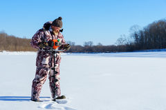 Bearded man is drilling ice hole by automatic moto boer for winter fishing at sunny day under blue sky Stock Image
