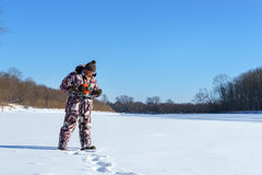 Bearded man is drilling ice hole by automatic moto boer for winter fishing at sunny day under blue sky Stock Photos