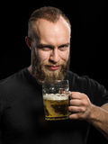 Bearded man drinking beer from a beer mug over black background. Stock Photos