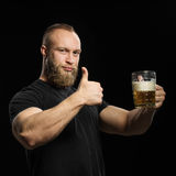 Bearded man drinking beer from a beer mug over black background. Royalty Free Stock Photo