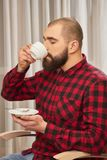Bearded man drinking coffee. Caucasian male holding white cup. The taste of manliness stock images