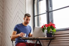 A man drinking coffee and using a laptop. Bearded man drinking coffee and using a laptop Royalty Free Stock Images