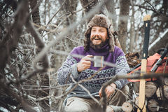 Bearded man drinking tea in the forest. Bearded woodcutter at rest in winter. Lunch have lumberjack winter Stock Photo