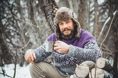 Bearded man drinking tea in the forest. Bearded woodcutter at rest in winter Royalty Free Stock Photography