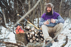 Bearded man drinking tea in the forest. Bearded woodcutter at rest in winter Royalty Free Stock Image