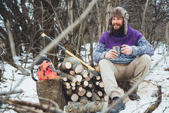 Bearded man drinking tea in the forest. Bearded woodcutter at rest in winter Stock Images