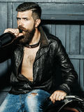 Bearded man drinks from bottle. Bearded man hipster biker with beard and moustache handsome stylish male in leather jacket drinks from bottle on motorcycle on Stock Image