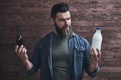 Bearded man with drinks. Bearded man is holding a bottle of milk in one hand and beer in another, on a wooden background stock image
