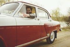 Bearded man driving a retro car Stock Photography