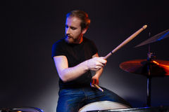 Bearded man drummer with closed eyes sitting and playing drums Stock Photography