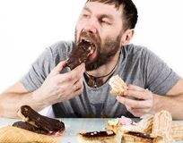 Bearded man eating cupcakes with pleasure after a diet. harmful but delicious food.  Royalty Free Stock Images