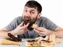 Bearded man eating cupcakes with pleasure after a diet. harmful but delicious food Stock Image