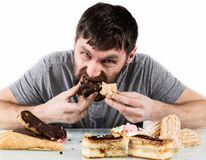 Bearded man eating cupcakes with pleasure after a diet. harmful but delicious food.  Stock Image