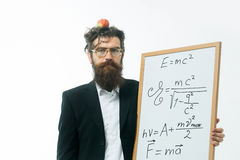 Bearded man with einstein formula and newtons law. Young handsome bearded man scientist or professor in glasses with long beard holding apple and teacher board Stock Photo