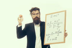 Bearded man with einstein formula and newtons law. Young handsome bearded man scientist or professor in glasses with long beard holding apple and teacher board Stock Photos