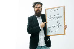 Bearded man with einstein formula and newtons law. Young handsome bearded man scientist or professor in glasses with long beard holding teacher board with Stock Photos