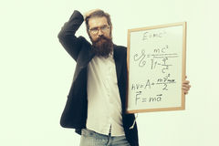 Bearded man with einstein formula and newtons law. Young handsome bearded man scientist or professor in glasses with long beard holding teacher board with Royalty Free Stock Photos