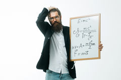 Bearded man with einstein formula and newtons law. Young handsome bearded man scientist or professor in glasses with long beard holding teacher board with Royalty Free Stock Photo