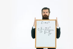 Bearded man with einstein formula and newtons law. Young handsome bearded man scientist or professor with long beard holding teacher board with einstein formula Royalty Free Stock Image
