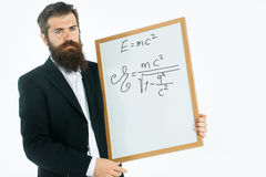 Bearded man with einstein formula and newtons law. Young handsome bearded man scientist or professor with long beard holding teacher board with einstein formula Stock Photo
