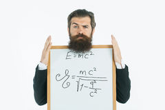 Bearded man with einstein formula and newtons law. Young handsome bearded man scientist or professor with long beard holding teacher board with einstein formula Stock Photography