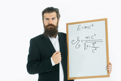 Bearded man with einstein formula and newtons law. Young handsome bearded man scientist or professor with long beard holding teacher board with einstein formula Royalty Free Stock Images