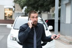 Bearded man emotionally talking on the phone. Near the car Royalty Free Stock Images