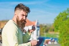 Bearded man with espresso mug, drinks coffee. Man with beard and mustache on strict face drinks coffee, urban background. Defocused. Coffee break concept. Man royalty free stock photo
