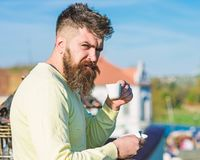 Bearded man with espresso mug, drinks coffee. Man with beard and mustache on strict face drinks coffee, urban background stock photo