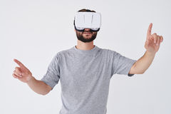Bearded man experiencing virtual reality pointed with hands. Close-up shot of bearded man experiencing virtual reality via VR glasses pointed with hands isolated Stock Images