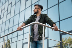 Bearded man in eyeglasses leaning on railing at office building. Young bearded man in eyeglasses leaning on railing at office building Stock Images