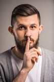 Bearded man. With finger on lips is keeping a secret Royalty Free Stock Photography
