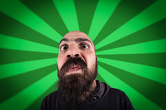Bearded man with funny expression. On a starburst background Royalty Free Stock Images