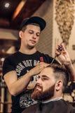 Bearded man getting beard haircut by hairdresser stock photo