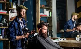 Bearded man getting groomed at hairdresser with hair dryer while sitting in chair at barbershop. Hipster concept stock photo