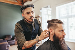 Bearded man getting haircut by barber stock photos
