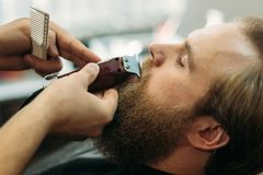 Bearded man getting a haircut by a professional hairdresser using comb and grooming scissors. Closeup view with shallow stock photos
