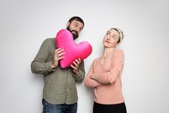 Bearded man gives red soft toy heart for his young girlfriend. Couple in love tears big heart on white background. Bearded men gives red soft toy heart for his royalty free stock photo