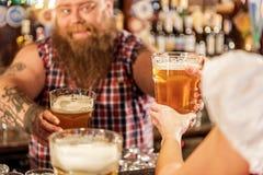 Bearded man giving drinks to waitress Royalty Free Stock Photo
