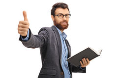 Bearded man giving a thumb up and holding a book Stock Image