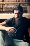 Bearded man with glass near wood piano Royalty Free Stock Photography