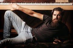 Bearded man with glass near wood piano Stock Image