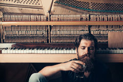 Bearded man with glass near wood piano Royalty Free Stock Photos