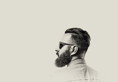 Bearded man with glasses. Black and white portrait of a Bearded Man in a denim shirt and glasses  on toned background. There is a spase for your text Royalty Free Stock Photos